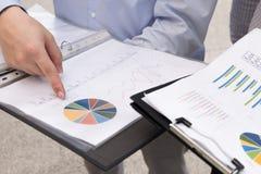 Las cartas y los gráficos de negocio se centran en señalar los fingeres Imagenes de archivo