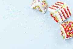 Las casas de pan de jengibre y la nieve asperja en el fondo azul CH Fotografía de archivo libre de regalías