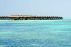 Las casas de planta baja del agua de un centro turístico isleño extienden en la laguna en el mA Foto de archivo libre de regalías