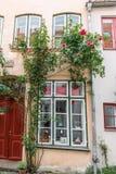 Las casas viejas hermosas en Luebeck adornaron con la flor color de rosa, Alemania Foto de archivo libre de regalías