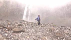 Las cascadas caen alto en las montañas La mujer va a caminar almacen de metraje de vídeo