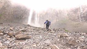 Las cascadas caen alto en las montañas La mujer va a caminar metrajes