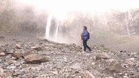 Las cascadas caen alto en las montañas La mujer va a caminar almacen de video