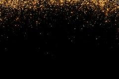 Las cascadas de las partículas de oro del champán de las burbujas de la chispa del brillo protagonizan en el fondo negro, día de  Foto de archivo
