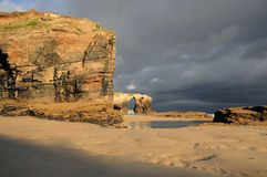 Las Catedrales beach. Ribadeo, Spain. Last ray of sun in the early morning before the rain Stock Image