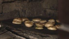 Las cebollas cortadas se fríen en parrilla de la barbacoa en horno de la albañilería sobre los carbones en la cocina del café en  almacen de metraje de vídeo