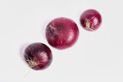 Las cebollas rojas en un fondo blanco, son Imagen de archivo