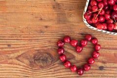 Las cerezas de cosecha propia orgánicas maduras en fondo de madera en corazón forman Foto de archivo libre de regalías