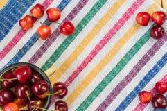 Las cerezas rojas y amarillas dispersaron en el mantel rayado Fotografía de archivo libre de regalías