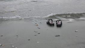 Las chancletas en la playa arenosa gris-amarilla cerca del mar agitan Concepto de las vacaciones almacen de video