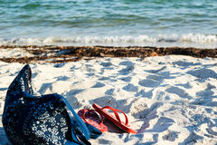 Las chancletas y una playa empaquetan en la arena blanca Fotos de archivo