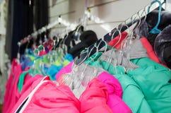 Las chaquetas coloridas calientes hermosas cuelgan en suspensiones dentro de la tienda de ropa Ropa hermosa para el otoño del inv Imagenes de archivo