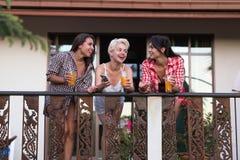 Las chicas jóvenes agrupan en balcón que hablan, comunicación hermosa de los amigos de la mujer Imagenes de archivo