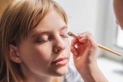 Las chicas j?venes aplican maquillaje a la cara imagenes de archivo