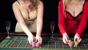 Las chicas jóvenes atractivas hacen apuestas en el casino back almacen de metraje de vídeo