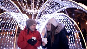 Las chicas jóvenes beben el café en el invierno en el centro de la ciudad, cerca de las decoraciones del invierno La Navidad, Año almacen de metraje de vídeo