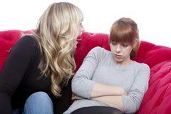 Las chicas jóvenes en el sofá rojo tienen una lucha Imagen de archivo libre de regalías