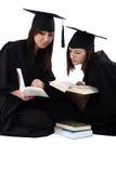 Las chicas jóvenes en estudiante cubren con la pila de libros Imagen de archivo