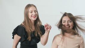 Las chicas jóvenes encantadoras están bailando y disfrutan en el fondo blanco almacen de video