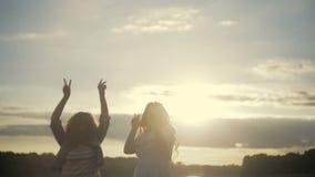 Las chicas jóvenes están teniendo un poco partido al lado del lago Baile, cantando en sol brillante Ropa de sport, vestido blanco almacen de metraje de vídeo