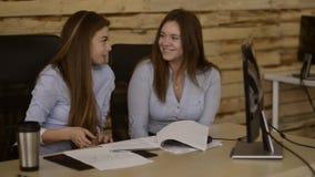 Las chicas jóvenes están trabajando en un desván mientras que discuten un proyecto Discusión de noticias de la compañía metrajes