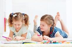 Las chicas jóvenes felices, niños que pintan con fieltro encierran juntas fotografía de archivo