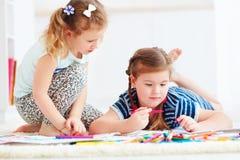 Las chicas jóvenes felices, niños que pintan con fieltro encierran juntas imagen de archivo