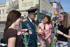 Las chicas jóvenes felicitan al veterano de la guerra Imagenes de archivo