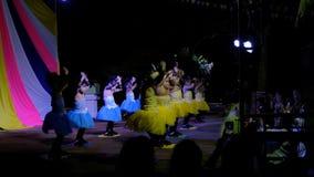 Las chicas jóvenes gozan el bailar juntas en etapa con el vestido colorido almacen de metraje de vídeo