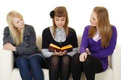 Las chicas jóvenes leyeron la ficción en el sofá Fotografía de archivo