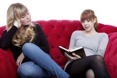 Las chicas jóvenes leyeron un libro en el sofá rojo Fotos de archivo