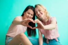 Las chicas jóvenes que muestran el corazón firman con sus manos que se sientan sobre fondo azul Foto de archivo libre de regalías