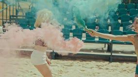 Las chicas jóvenes se divierten con humo coloreado y saltan al aire libre en la cámara lenta almacen de metraje de vídeo