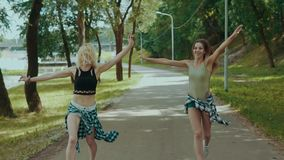Las chicas jóvenes se divierten y al aire libre en la cámara lenta Mujer en funcionamientos de los pantalones cortos en parque metrajes