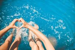Las chicas jóvenes se sientan al borde de piscina y de charla con sus pies en el agua y llevan a cabo sus manos en corazón imagen de archivo
