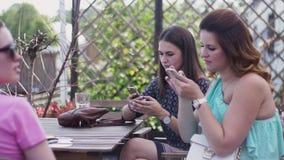Las chicas jóvenes se sientan en la terraza del restaurante Smartphones Mujer embarazada holidays metrajes