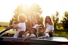 Las chicas jóvenes y los individuos elegantes hermosos en gafas de sol son que se sientan y de risas en un cabriolé negro en un d imagen de archivo