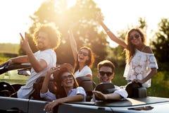 Las chicas jóvenes y los individuos elegantes hermosos en gafas de sol son que se sientan y de risas en un cabriolé negro en un d fotografía de archivo
