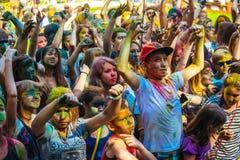 Las chicas jóvenes y los muchachos participan en festival del color de Holi Imágenes de archivo libres de regalías