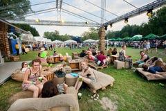 Las chicas jóvenes y los muchachos se divierten con los amigos y las bebidas al aire libre Foto de archivo