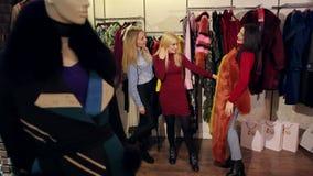 Las chicas j?venes intentan encendido un abrigo de pieles de moda en una tienda de la moda metrajes