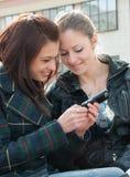 Las chicas jóvenes miran algo en teléfono móvil Fotos de archivo libres de regalías