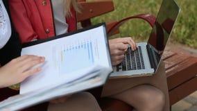 Las chicas jóvenes que se sientan juntas en banco en parque y que usan el ordenador portátil consiguen la información primer almacen de video