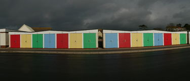 Las chozas coloridas de la playa en Inglaterra fotografiaron contra un cielo tempestuoso Fotos de archivo libres de regalías