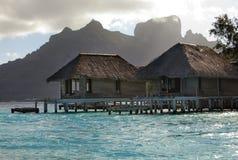 Las chozas lanzadas destruidas en el agua y la isla con las palmeras en el océano y montañas en un fondo Imágenes de archivo libres de regalías