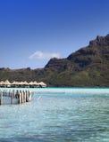Las chozas lanzadas destruidas en el agua y la isla con las palmeras en el océano y montañas en un fondo Fotos de archivo libres de regalías