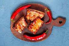Las chuletas de cerdo asadas a la parrilla calientes picantes del Bbq sirvieron con pimienta del chile picante en el tablero de m fotografía de archivo