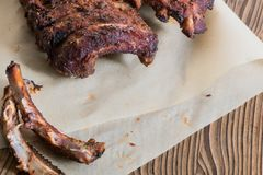 Las chuletas de cerdo asadas a la parrilla con los huesos roídos en el papel apoyado - copie el espacio fotografía de archivo libre de regalías
