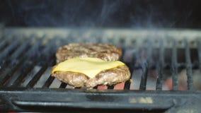 Las chuletas del cheeseburger se asan a la parrilla con queso almacen de video