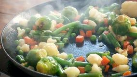 Las chuletas y las verduras se fríen en aceite de girasol en sartén Primer Haba, zanahorias, coliflor almacen de video
